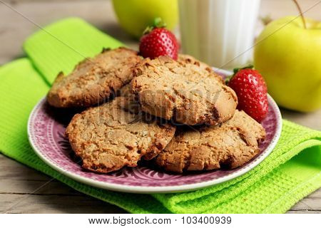 Homemade cookies with fruits and glass of milk on table close up