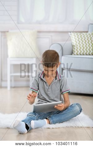 Little boy with digital tablet sitting on carpet, on home interior background