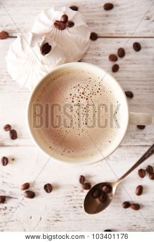Cup of coffee with beans and zephyr on wooden table, top view