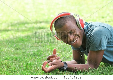 Handsome African American man with headphones lying on green grass