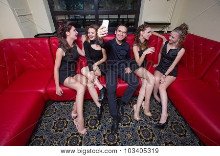a man photographed on the phone. next four girls.