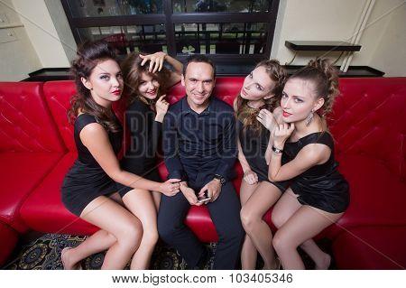 a man holding a cell phone. next four girls.