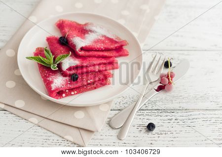 beet pancakes with powdered sugar and berries on wooden background.