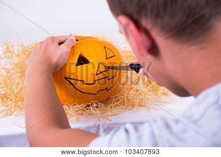 Man With Knife Preparing Pumpkin For Halloween
