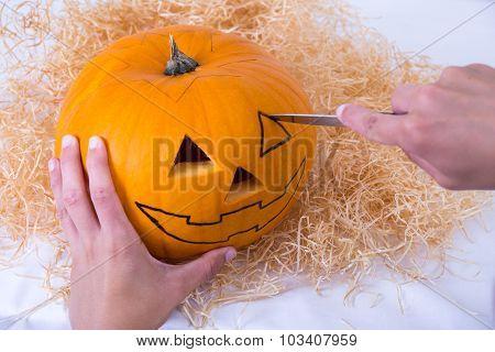 Male Hand Making Pumpkin Jack O'lantern For Halloween