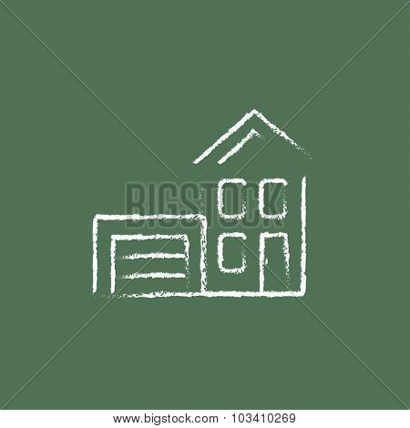 House with garage hand drawn in chalk on a blackboard vector white icon isolated on a green background.