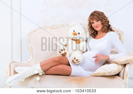 Redheaded Pregnant Girl In A Knitted Dress With Teddy Bear On The Couch