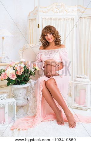 Redheaded Pregnant Girl Sitting On Chair And Hugging Tummy With Love