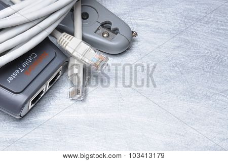 Network tester and crimping tool with RJ45 connector on metal background
