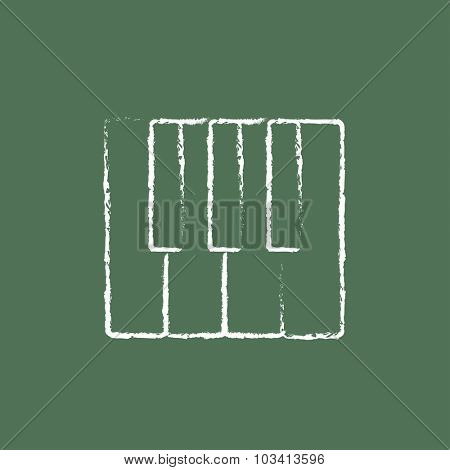 Piano keys hand drawn in chalk on a blackboard vector white icon isolated on a green background.