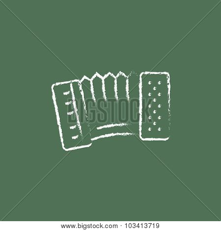 Accordion hand drawn in chalk on a blackboard vector white icon isolated on a green background.