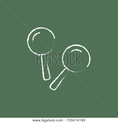 Maracas hand drawn in chalk on a blackboard vector white icon isolated on a green background.