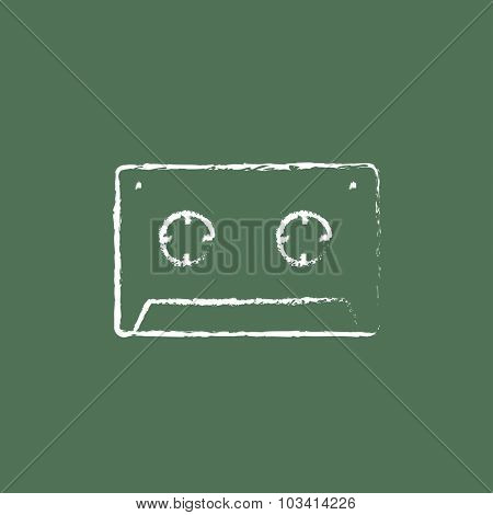 Cassette tape hand drawn in chalk on a blackboard vector white icon isolated on a green background.