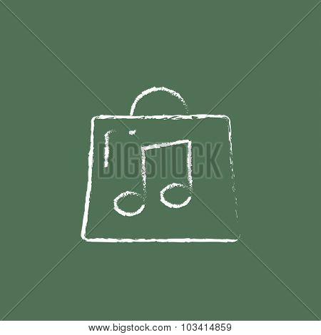 Bag with music note hand drawn in chalk on a blackboard vector white icon isolated on a green background.