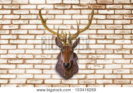 Deer Head Made Of Red Wood On Blurred White Brick Wall Background.