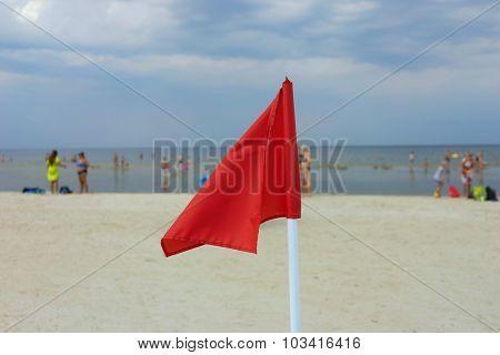 Red Flag On A Sandy Beach