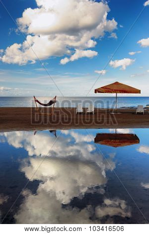Hammock With An Umbrella And Chairs On A Narrow Strip Of Sand On