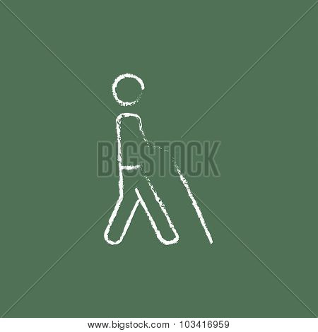 Blind man with stick hand drawn in chalk on a blackboard vector white icon isolated on a green background.