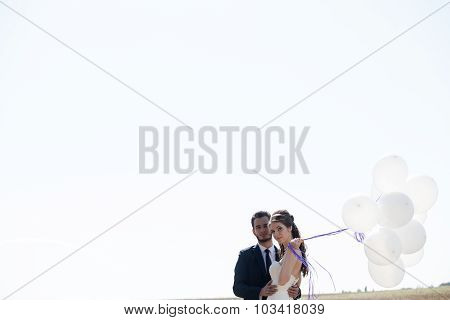 Girl In Wedding Dress And Husbad With Ballons In Hands