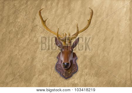 Deer Head Made Of Red Wood On Blurred Concrete Wall Background.
