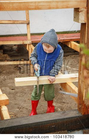 Little Studious Boy Sawing A Wooden Board. Home Construction. Little Builder.