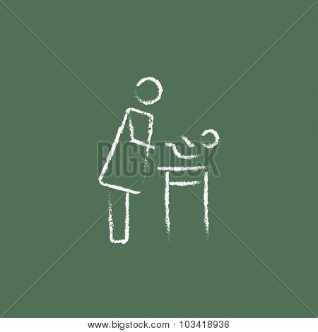 Mother taking care of the baby hand drawn in chalk on a blackboard vector white icon isolated on a green background.