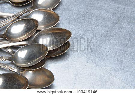 Vintage silver teaspoons on metal table