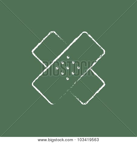 Adhesive bandages hand drawn in chalk on a blackboard vector white icon isolated on a green background.