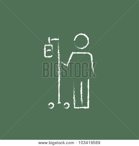 Patient standing with intravenous dropper hand drawn in chalk on a blackboard vector white icon isolated on a green background.
