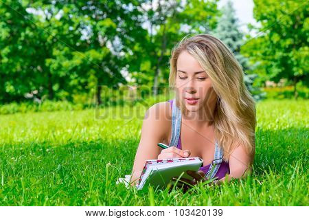 Attractive Young Woman Making Notes In A Notebook Lying On The Grass