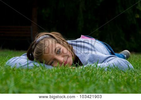 Happy child girl laying in grass