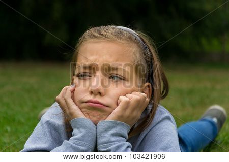 Sad and angry child lay in garden