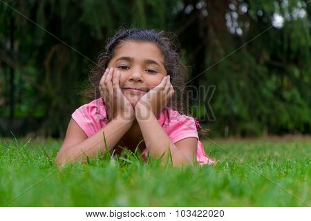 Small Gypsy Child Girl Lay In Grass Having Head In Hands