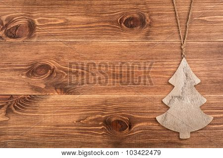 Christmas decorative wooden fir-tree on the wooden background.