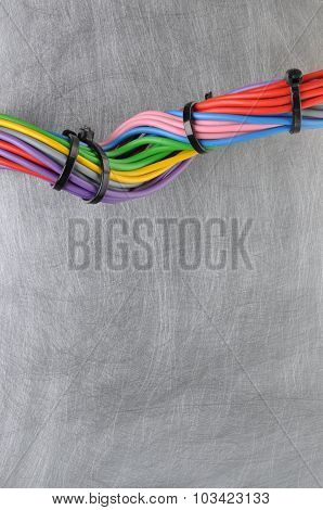 Multicolored electric cables on gray metal surface with place for text