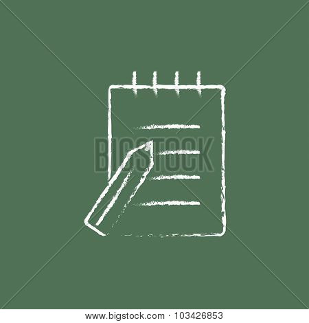 Writing pad and pen hand drawn in chalk on a blackboard vector white icon isolated on a green background.