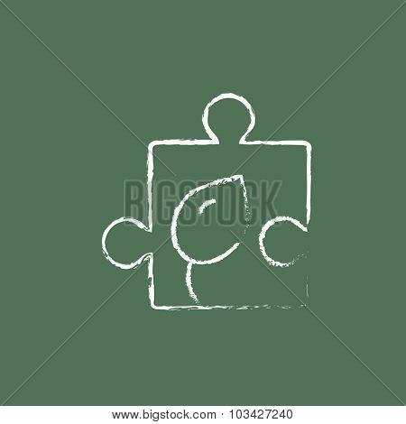 Puzzle with leaf hand drawn in chalk on a blackboard vector white icon isolated on a green background.