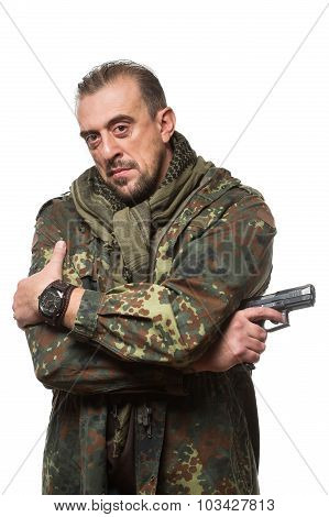 Male terrorist in a military jacket with a gun in his hand.