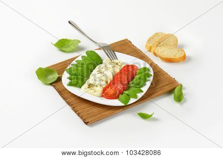 plate of fresh caprese salad with bread on brown place mat