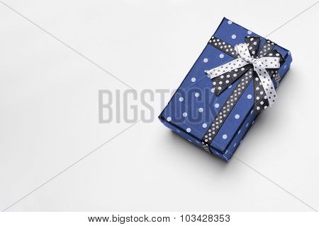 Small blue gift box with ribbon and circles top