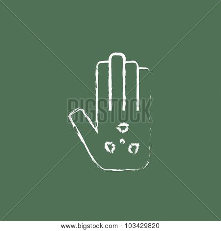Ionizing radiation sign on a palm hand drawn in chalk on a blackboard vector white icon isolated on a green background.