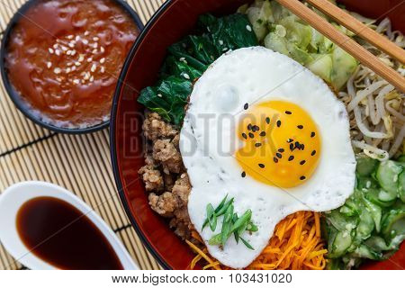 Korean cuisine, beef  Bibimbap in a clay pot on bamboo
