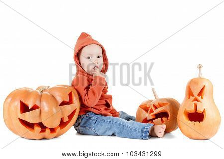 Halloveen small boy sits surrounded by pumpkins on white background
