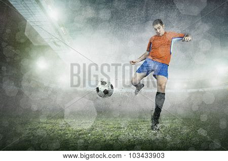 Soccer player with ball in action at stadium under rain.