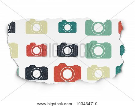 Tourism concept: Photo Camera icons on Torn Paper background