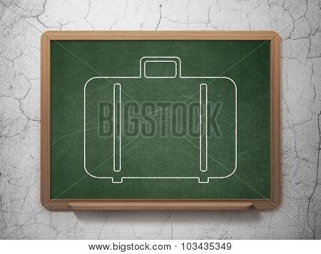 Travel concept: Bag on chalkboard background