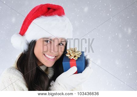 Smiling teen girl wearing a Santa Claus hat holding a small Christmas present up to her face. Horizontal format with snowy background.