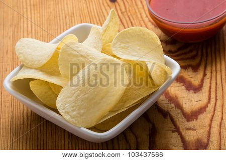 Potato Chips With Dip On A Wooden Table