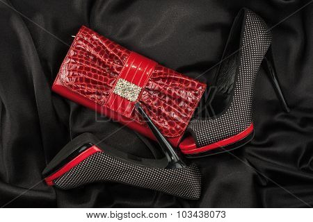 Black shoes and purse  lying on black satin