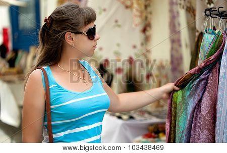 woman is choosing a scarf in a street shop